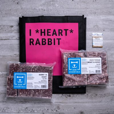 "Assortment Of Raw Essential Products For Cats Including, Pink And Black Tote Bag With ""I *Heart* Rabbit"" Written,  Sample Bag Of Power Mix, 1KG Plastic Pack Of Cubed Rabbit Heart Meat Mix, 1KG Plastic Pack Of Cubed Duck Tongue, Heart And Kidney Meat Mix"